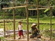 Construyendo una cabaña en compañia de su nieto. Indonesia