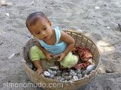 Niño dentro del capazo con caracolas para vender. Lombok.Indonesia