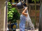 Mujer lavandose con la tecnica del cubo. Lombok. Indonesia.