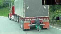 ciclista cogido a un camion y transportado sin esfuerzo pero con peligro