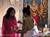 Mujer hindú haciendo una ofrenda con el sacerdote.